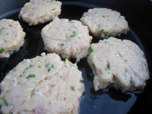 Use a spatula to carefully move the fish patties from the baking sheet to the hot oil.