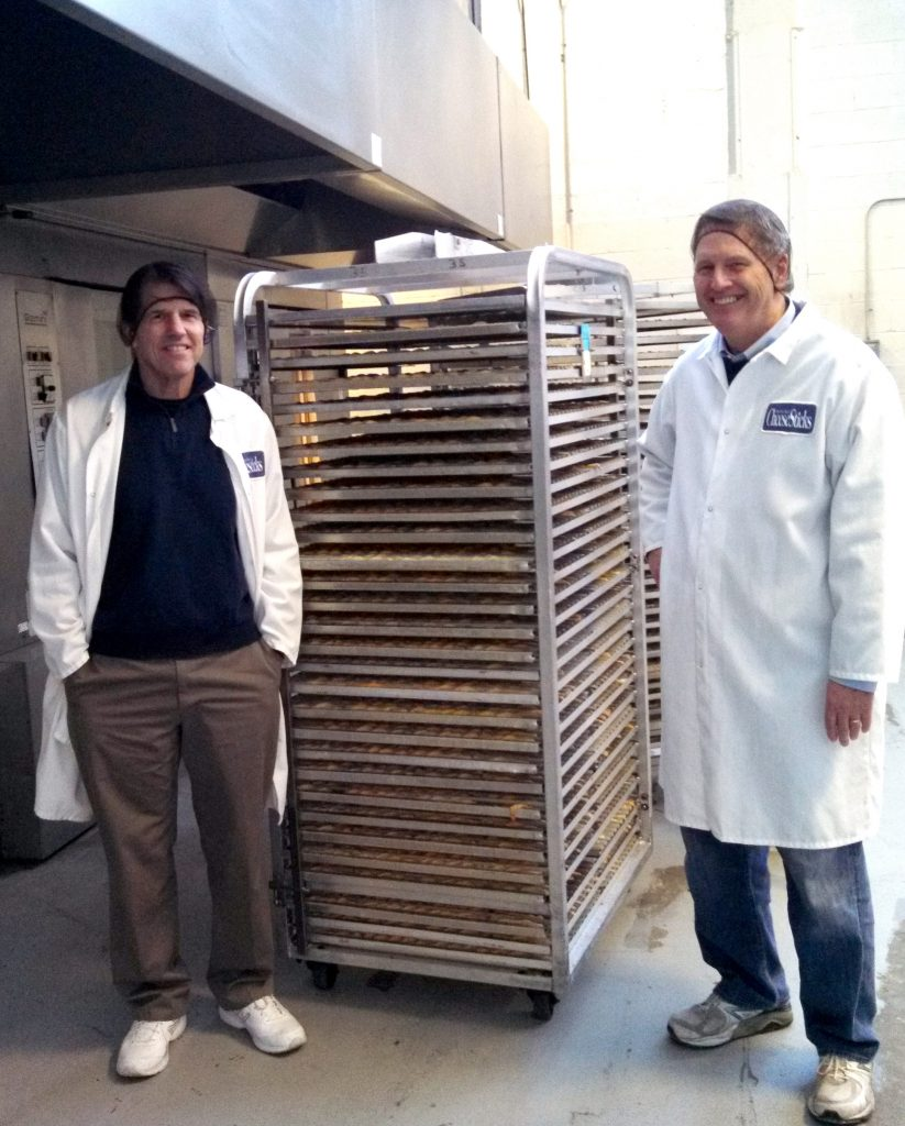 CheeseSticks founder, John (on the left) and his brother Tim, next to a tray of freshly baked product.