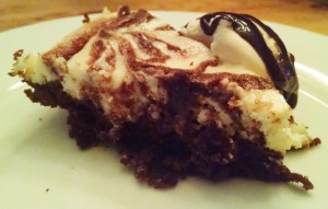A wedge of extra moist, fudgy chocolate and cheesecake brownie - served with ice cream and chocolate syrup. So good!