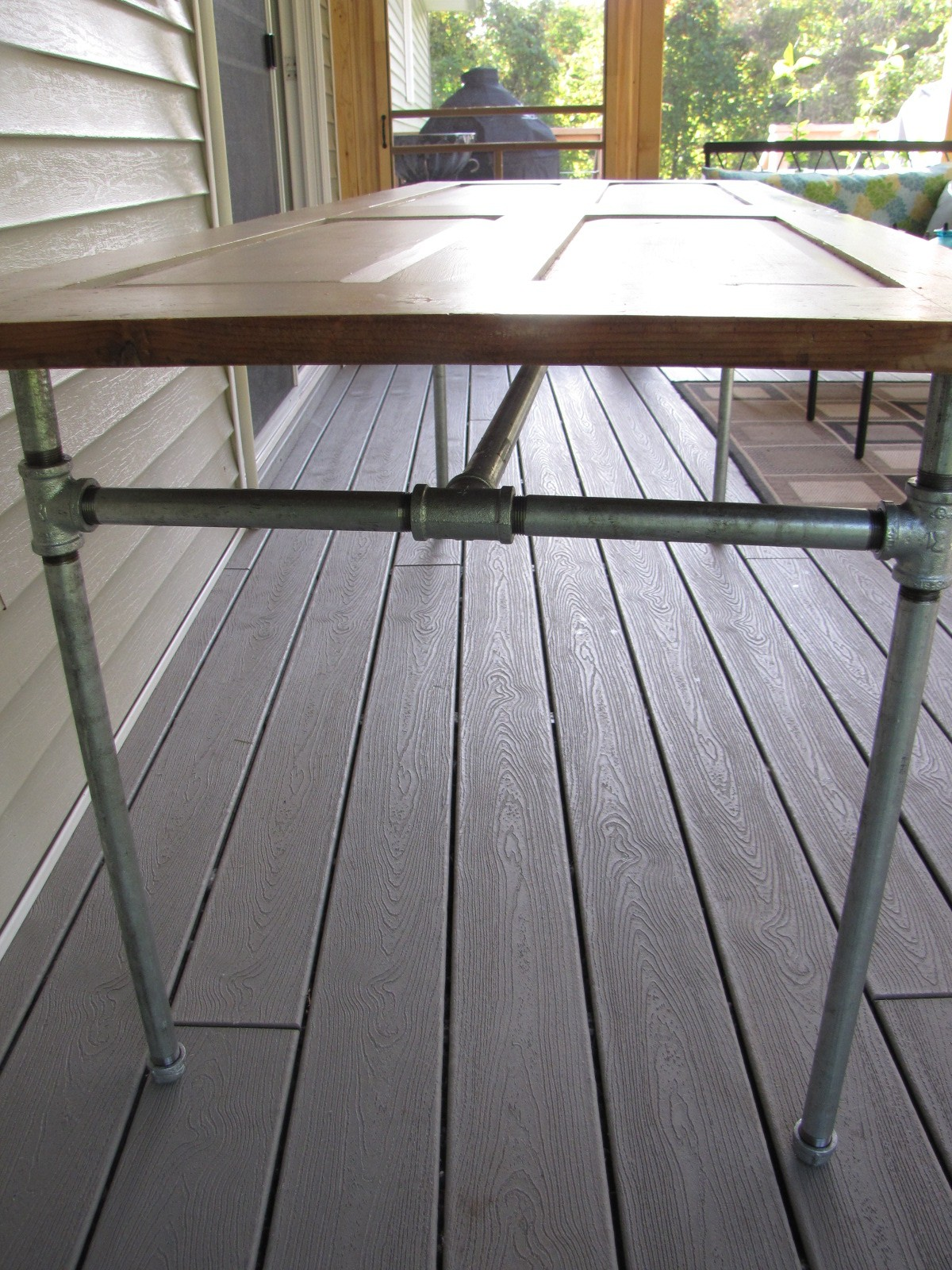 diy table made from an door and galvanized pipe